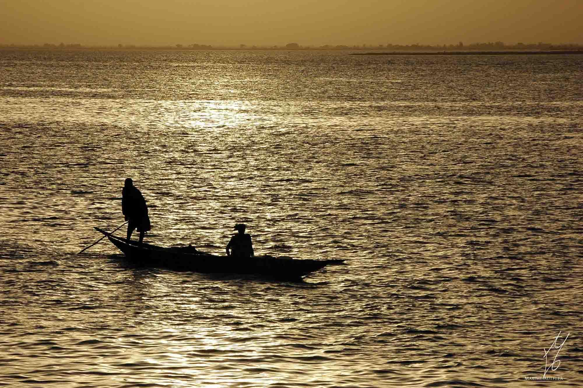 Photographie d'une embarcation sur le Niger au coucher de soleil