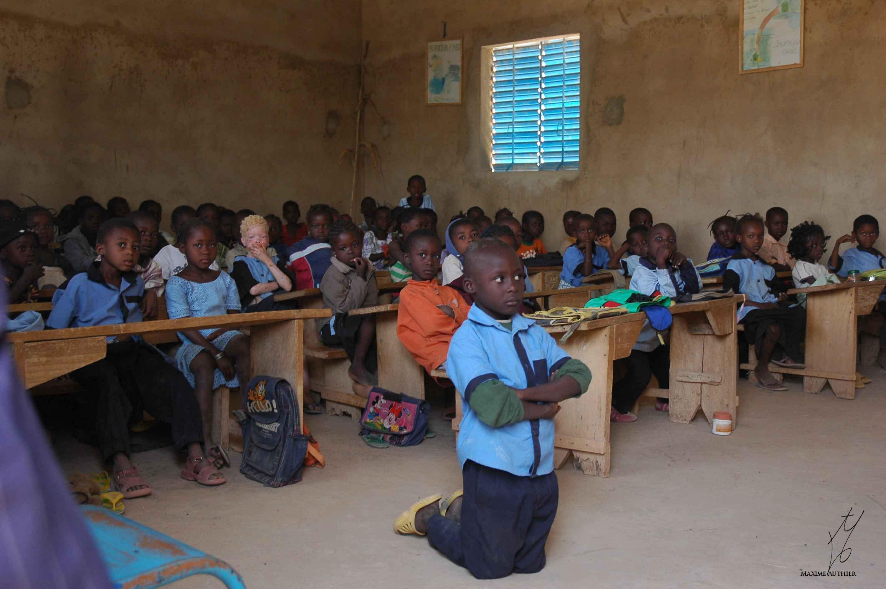 photographie d'un garçon puni en classe en Afrique